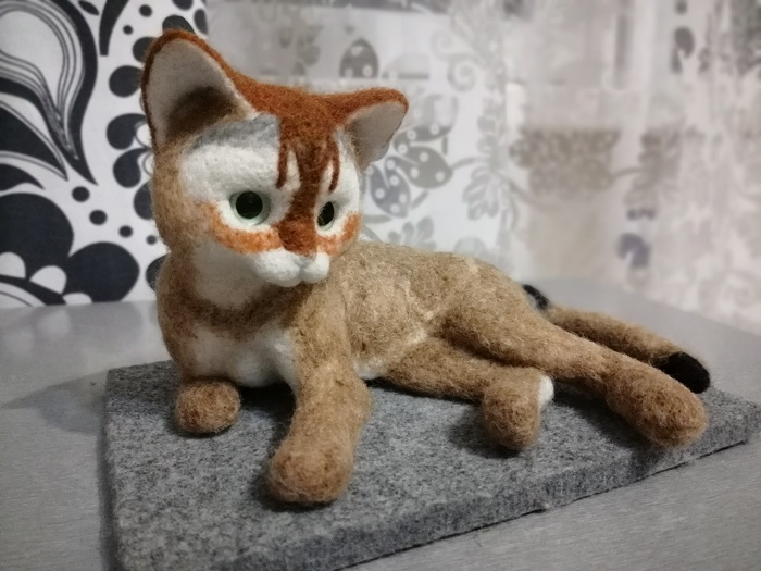 котенок с перышком из шерсти